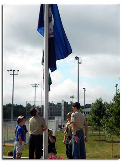 Boy Scouts stand at the base of a flagpole